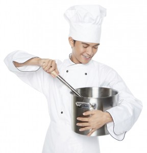 Male chef stirring food in the pot